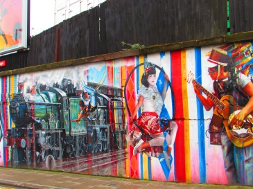 Three graffiti paintings, a green steam train, a pale woman with dark hair and a white top and red sarong swinging on a suspended hoop and a man with a hat playing an acoustic guitar